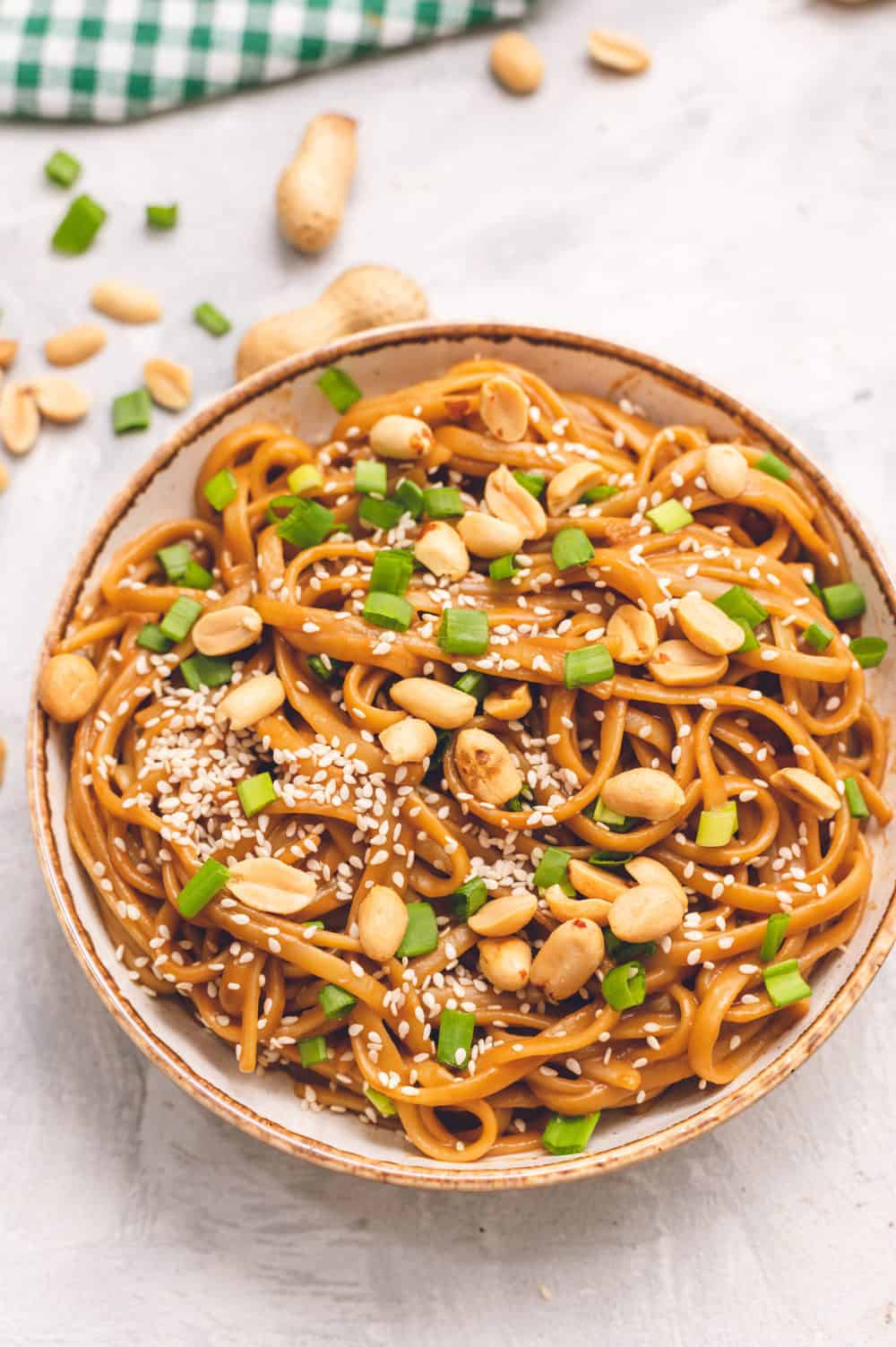 Thai peanut sesame noodles in a bowl with peanuts and onions garnished over top.