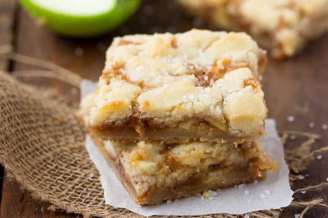 Salad caramel apple butter bars stacked on top of each other with parchment paper underneath.