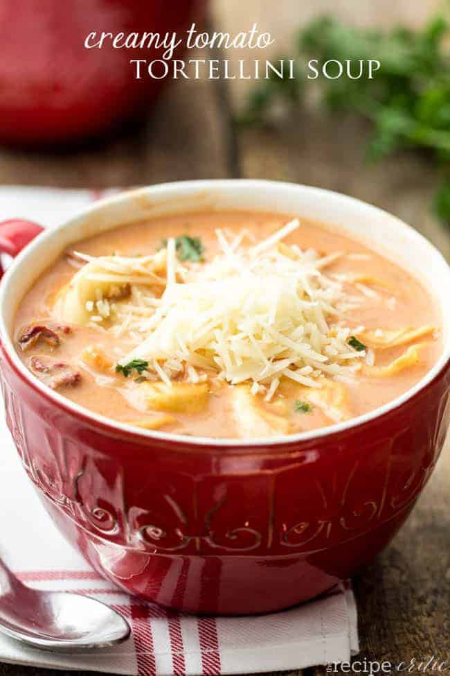 Creamy tomato tortellini soup in a red bowl garnished with shredded parmesan cheese.