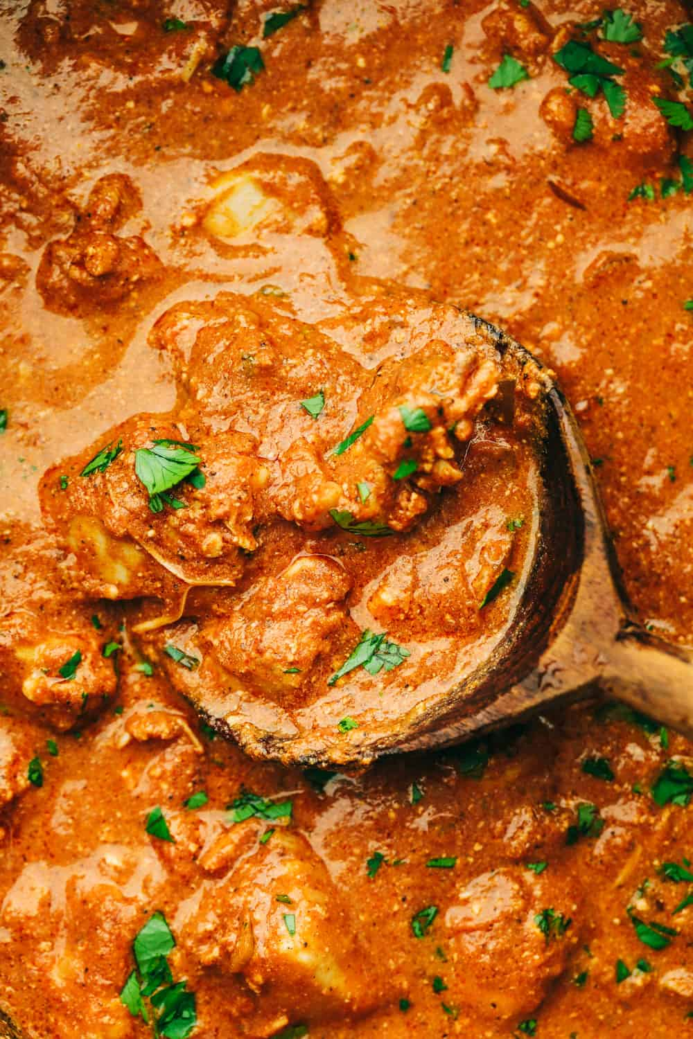 Chicken tikka masala on a spoon showing the chicken and orange colored sauce.