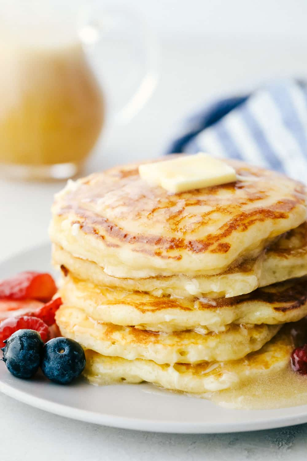 Fluffy Buttermilk pancakes on a plate with butter and syrup.