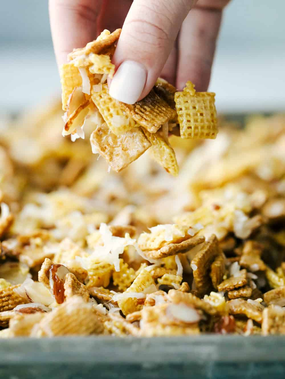 ooey gooey Chex mix on a sheet pan with Alyssa, the recipe critic showing it in her fingers.