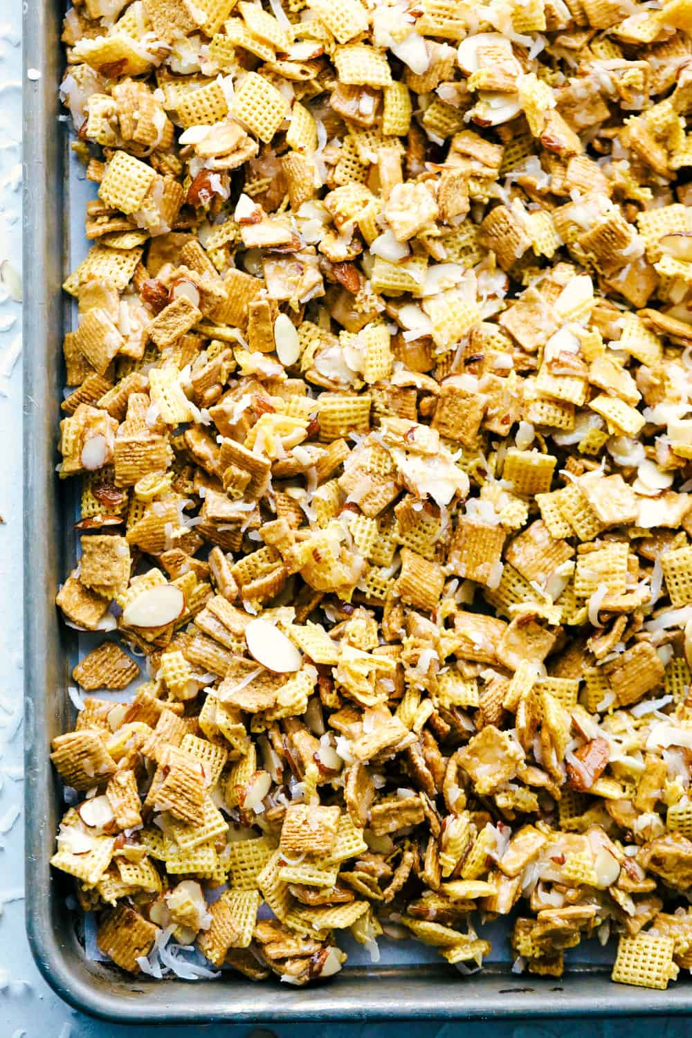 ooey gooey Chex mix on a sheet pan.