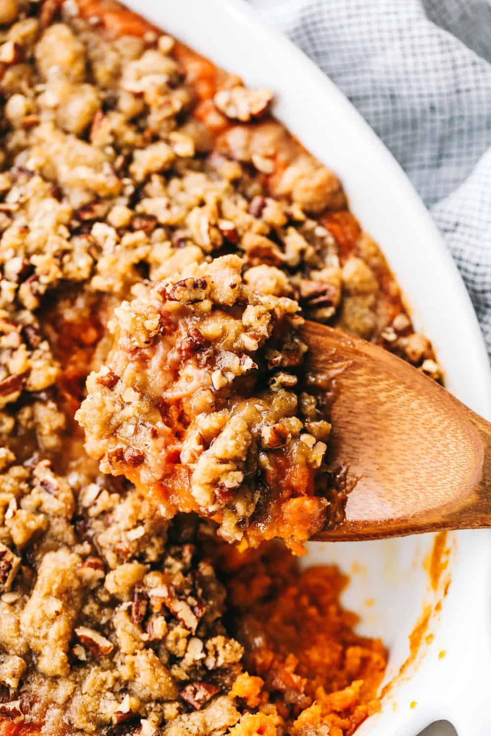 baked sweet potato casserole with a wooden spoon
