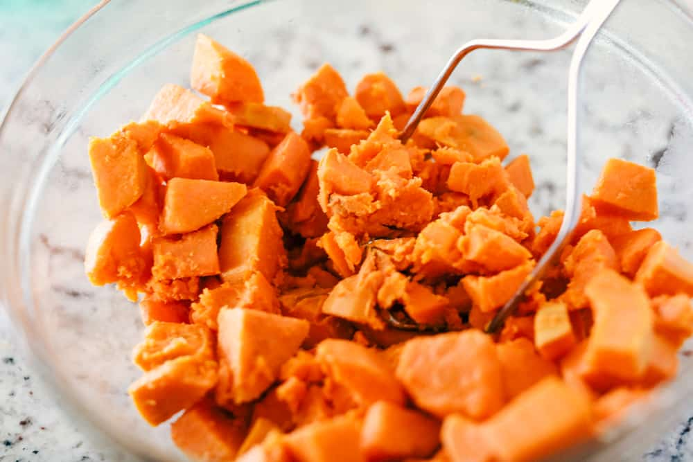sweet potatoes being mashed in a bowl with a potato masher