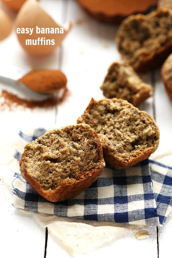 Easy Banana Muffins broken in half and on a blue and white cloth.