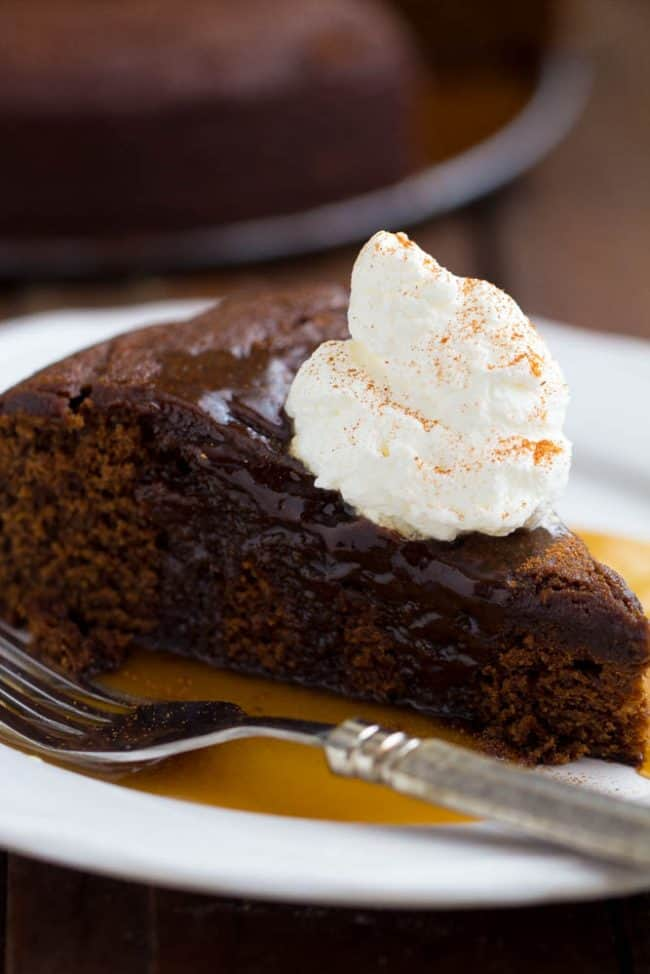 A slice of chocolate cake with caramel sauce over top and a dollop of cool whip on top with a fork on the side,