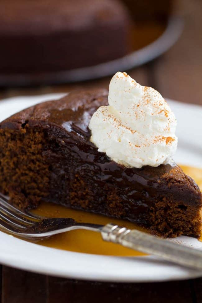 A slice of warm chocolate caramel cake with whip cream on top on a white plate with a fork on the side.