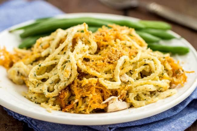 Cheesy Cheddar Chicken Spaghetti Casserole on a white plate with green beans on the side.