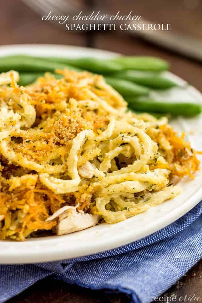 Cheesy Cheddar Chicken Spaghetti Casserole on a white plate with green beens on the side.
