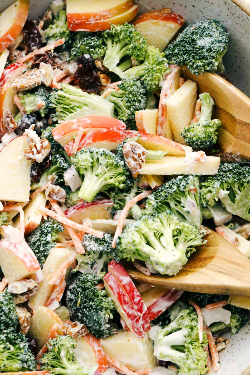 Upclose picture of broccoli apple salad with pecans, raisins and dressing.