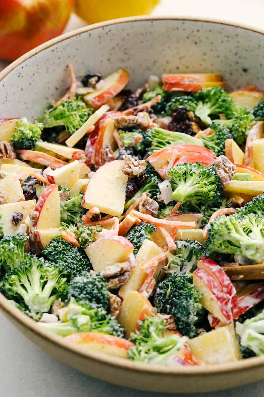 Salada de maçã com brócolis com molho picante em uma tigela pronta para comer.