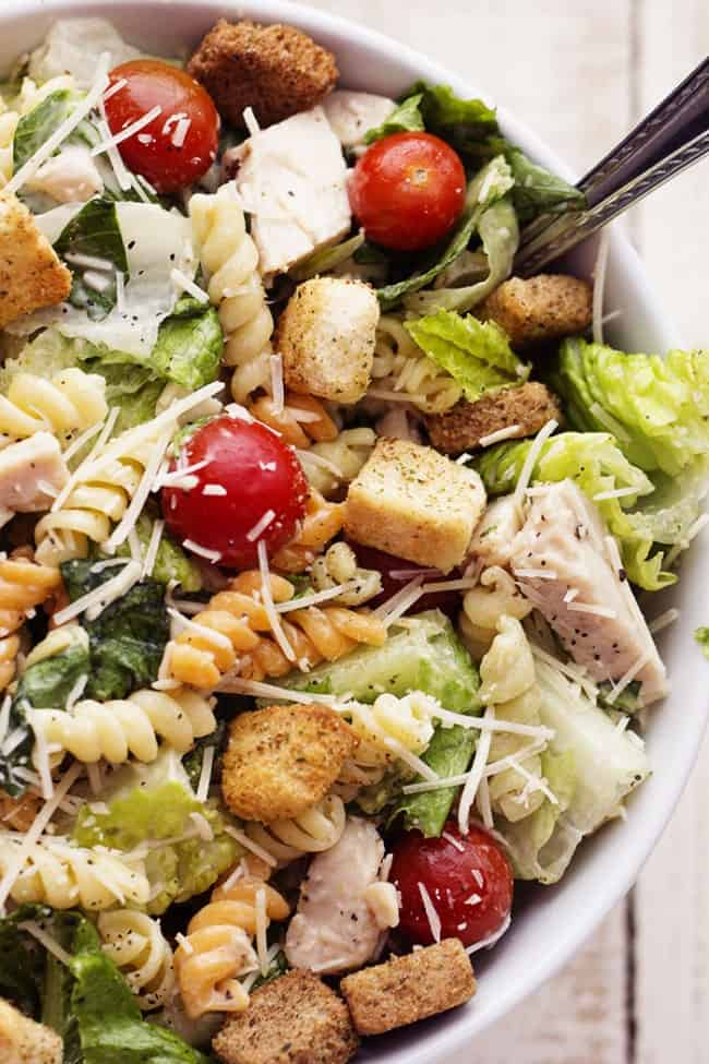 Chicken Caesar salad in a white serving bowl garnished with tomatoes and cheese.