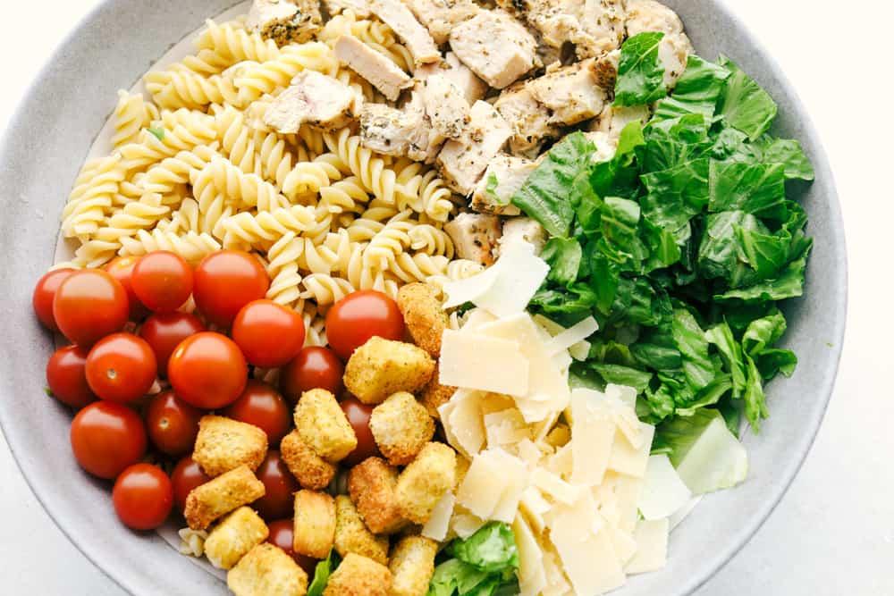 Alle ingrediënten voor Chicken Pasta Caesar Salad zijn klaar om gemengd te worden.