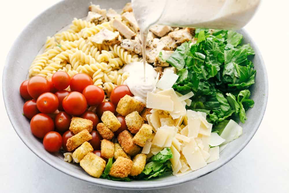 Giet de dressing over de salade.