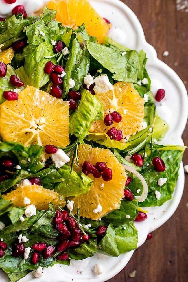 Orange pomegranate salad on a white decorative plate.
