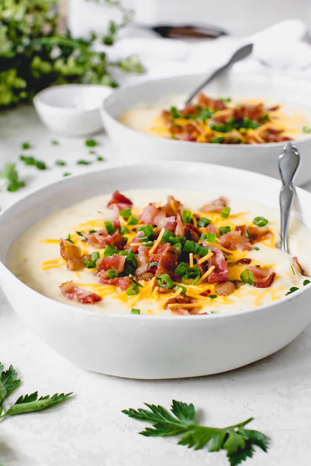 Two bowls full of loaded baked potato with a spoon garnished with chopped bacon, cheese and green onions.