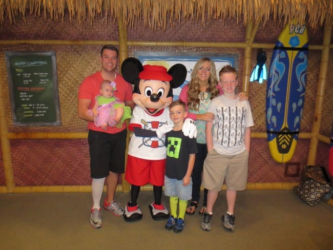 A family photo with Mickey Mouse at a Disneyland restaurant.