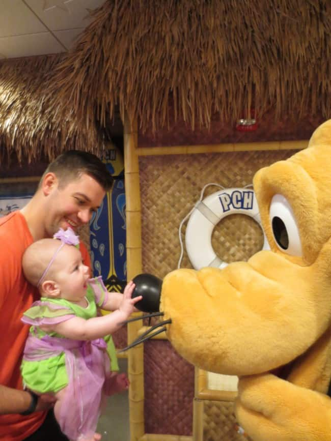A photo with my husband and baby girl talking and touching Plutos nose.