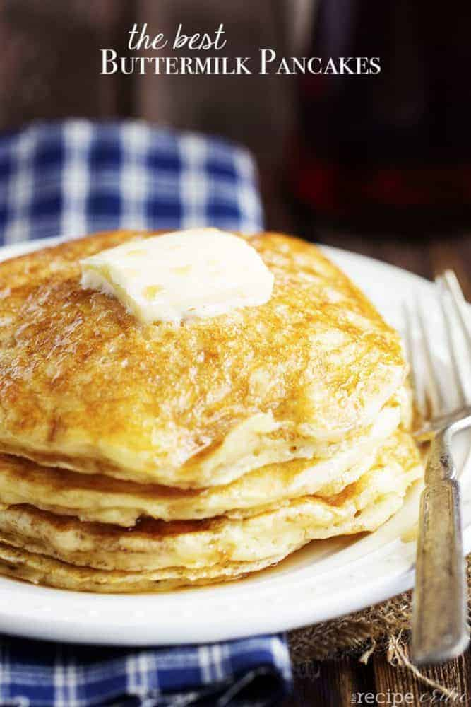 Buttermilk pancakes stacked on top of each other with a slice of butter on top and a fork on the side of a white plate.