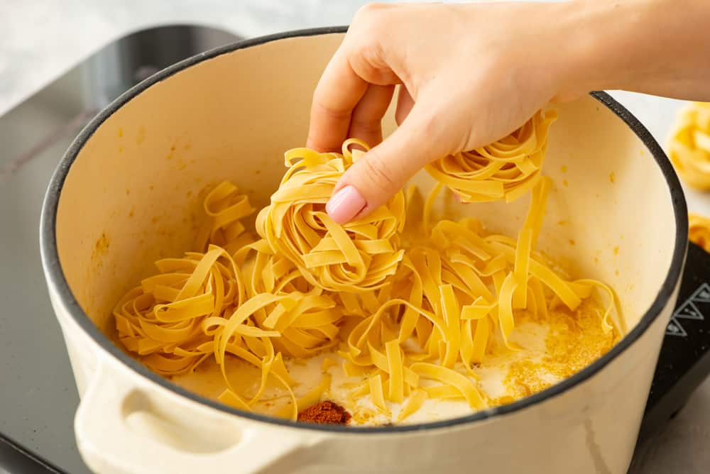 dried fettuccine noodles being added to the pot to cook