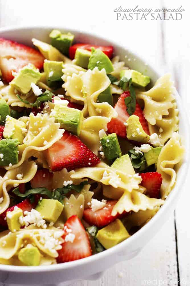 strawberry avocado pasta salad in a white serving bowl.