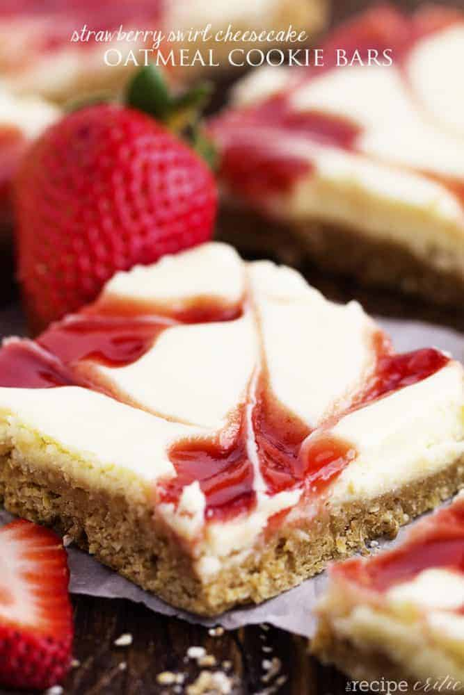 strawberry swirl cheesecake oatmeal cookie bar close up with a strawberry garnish.
