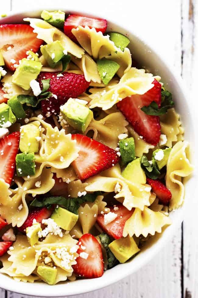 strawberry avocado pasta salad in a white bowl.