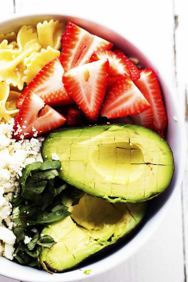strawberry avocado pasta salad ingredients in a white bowl.