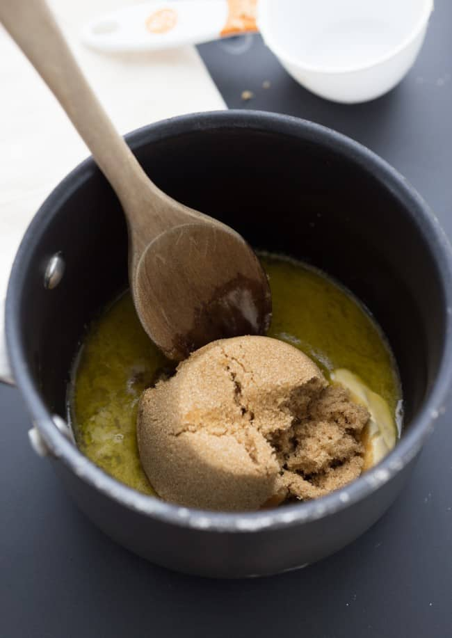Brown sugar and butter in a large pot with a wooden spoon.