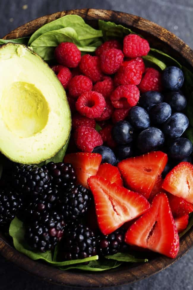 Berry Avocado salad ingredients in a wooden bowl.