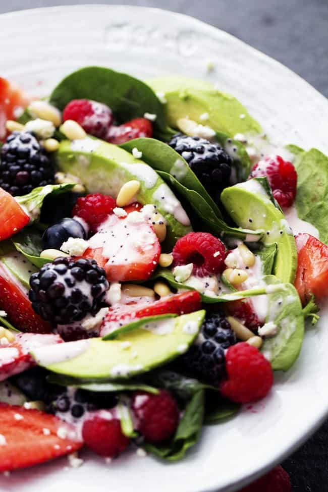 Close up of a berry salad on a white plate.