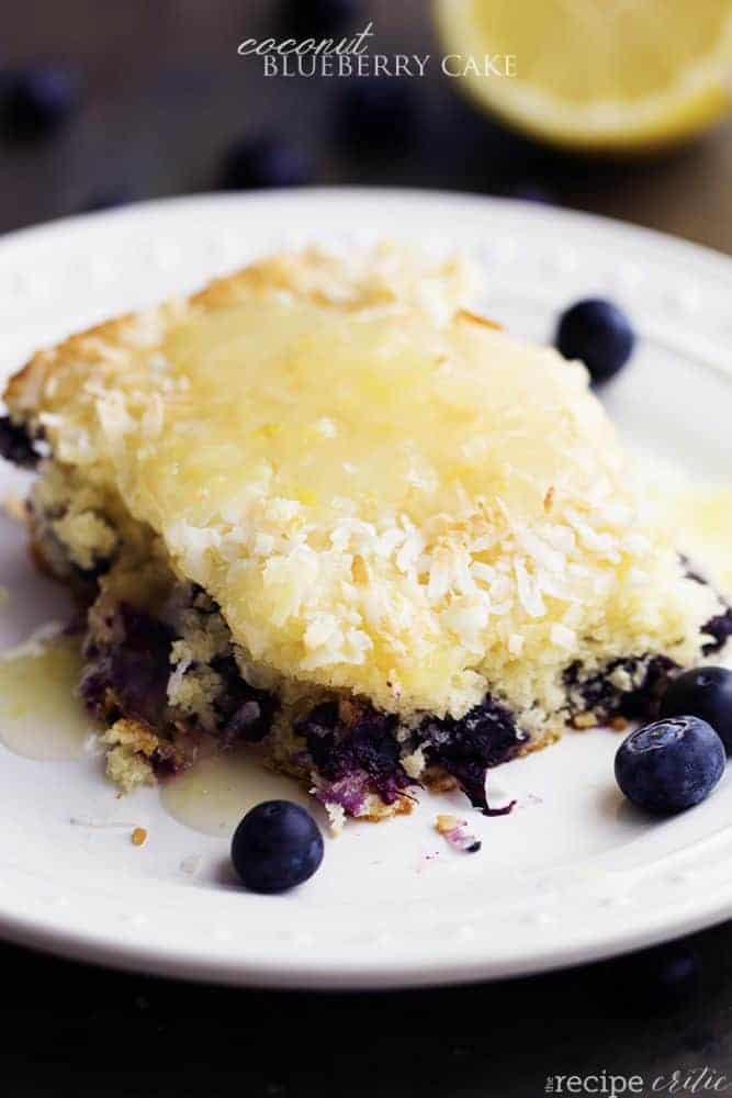 coconut blueberry cake serving on a white plate with blueberries for garnish.