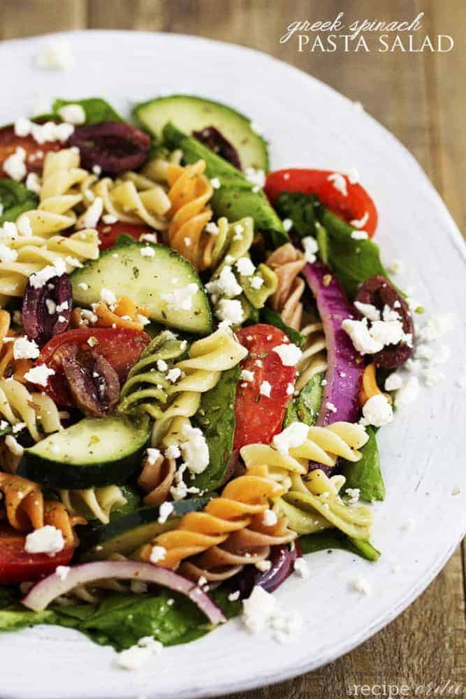 Greek spinach pasta salad on a white plate.