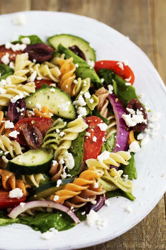 greek spinach pasta salad in a white bowl.