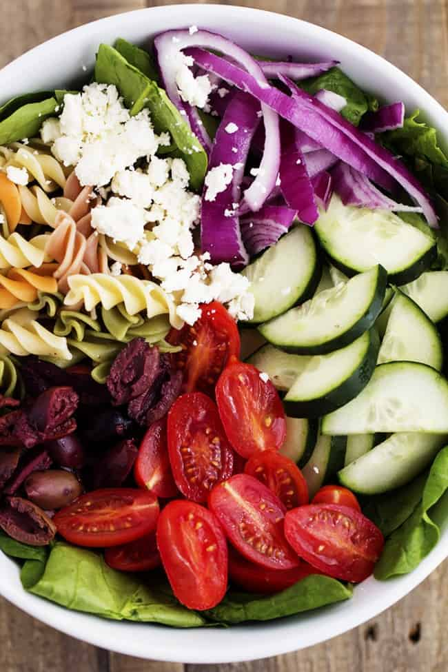 greek spinach pasta salad ingredients in a white bowl.