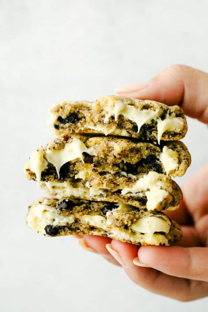 White chocolate oreo cookies stacked on top of each other and being held up with a hand.