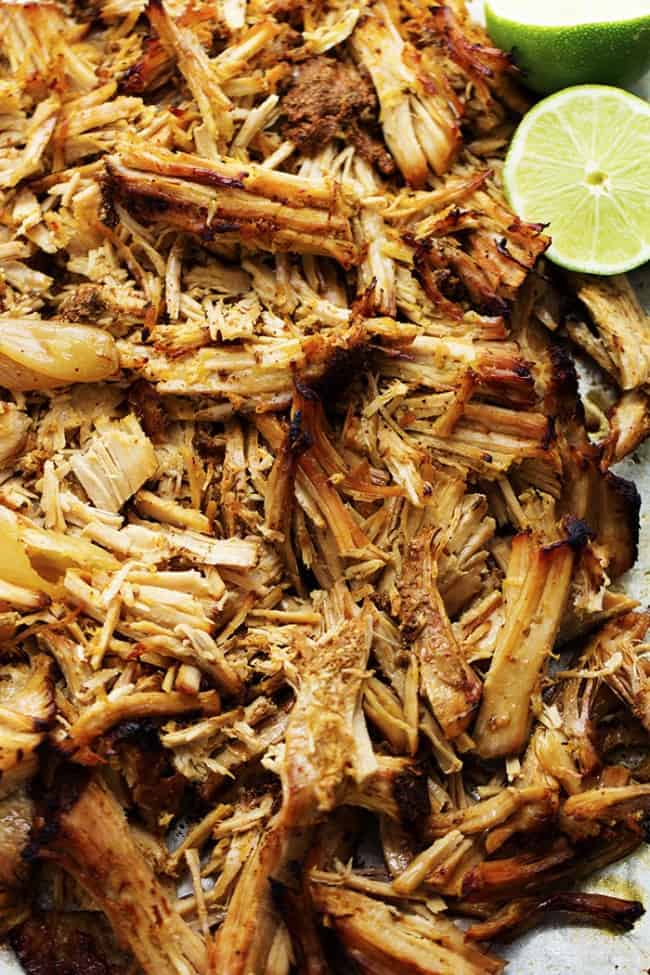 Slow cooker pork carnitas with lime garnish.