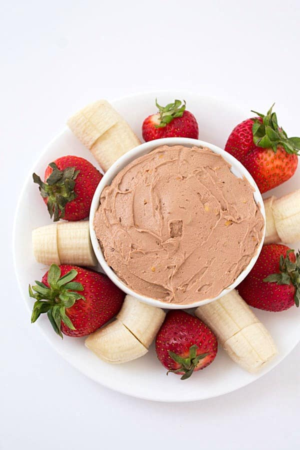 Peanut butter fruit dip in a white bowl with strawberries and bananas around it.