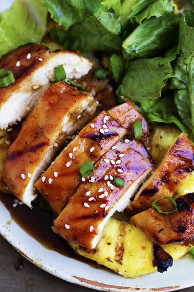 Grilled pineapple teriyaki chicken with salad and pineapple on a white plate.