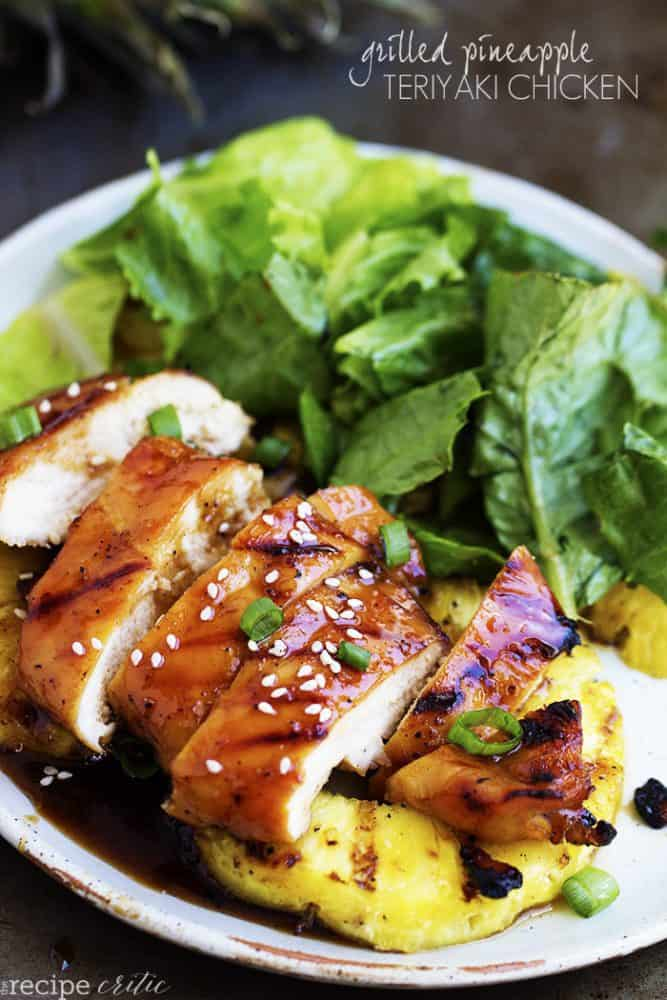 grilled pineapple teriyaki chicken on a white plate with pineapple and salad.