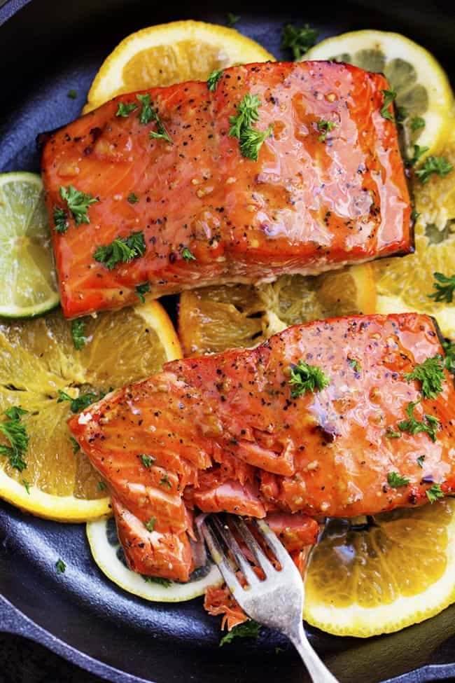 grilled citrus salmon on lemon slices in a skillet being cut into by a fork.