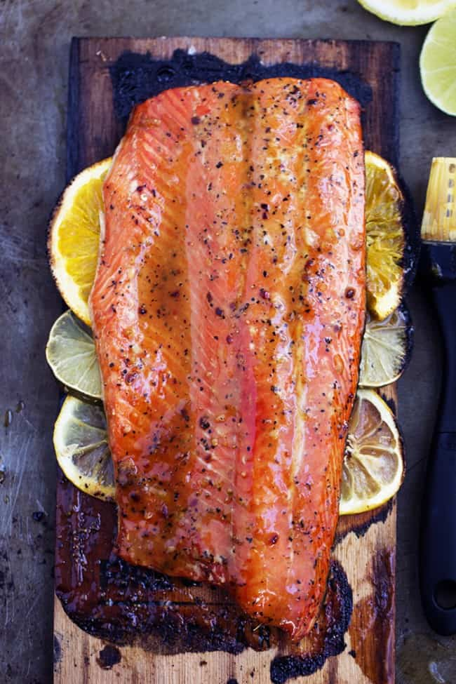 grilled triple citrus salmon on lemon slices on a wooden plank.