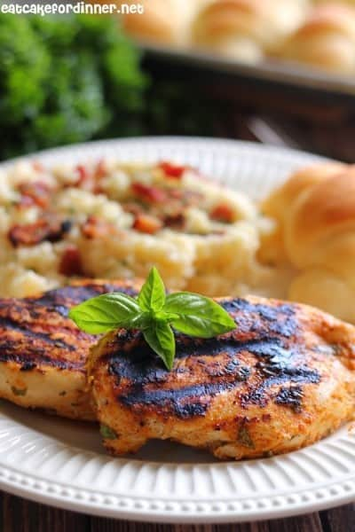 grilled basil rub chicken on a white plate.