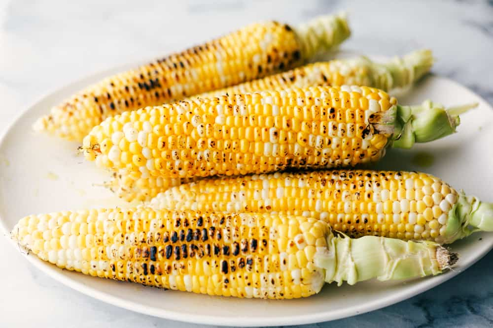 Grilled corn stacked on a white plate.