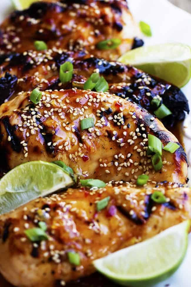sweet chili lime chicken close up with lime and sesame seed garnish.