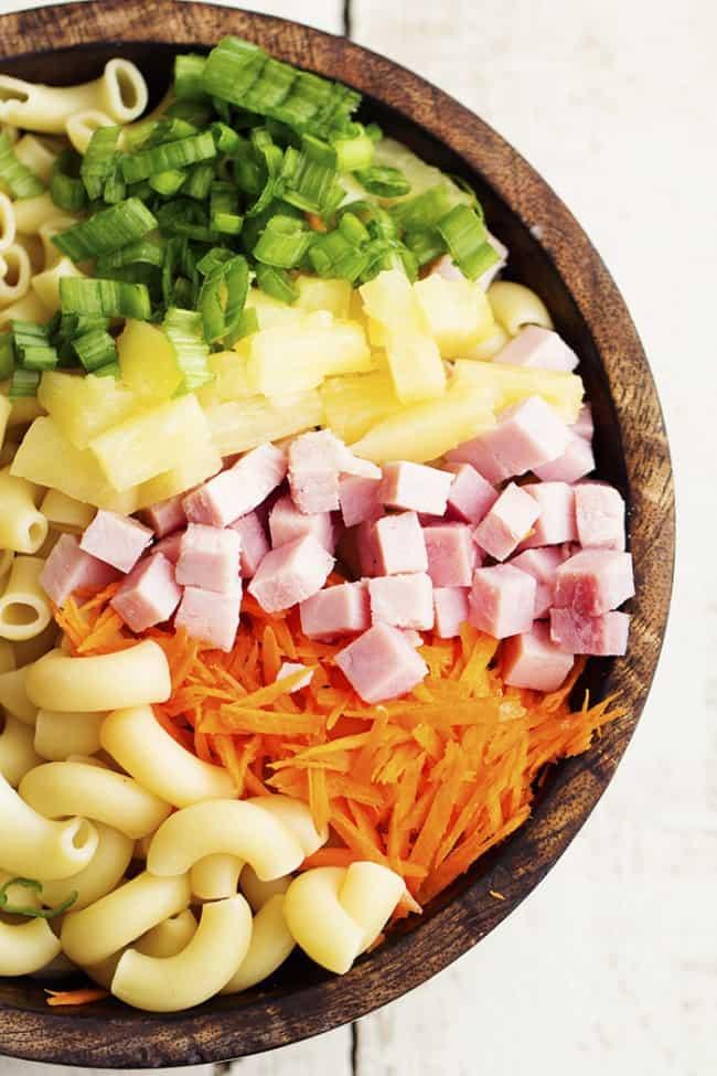 hawaiian macaroni salad ingredients in a wooden bowl.