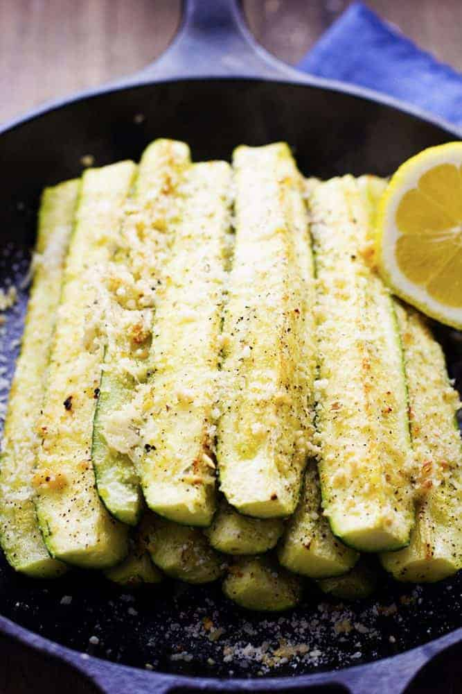 roasted lemon parmesan garlic zucchini spears stacked in a black skillet.
