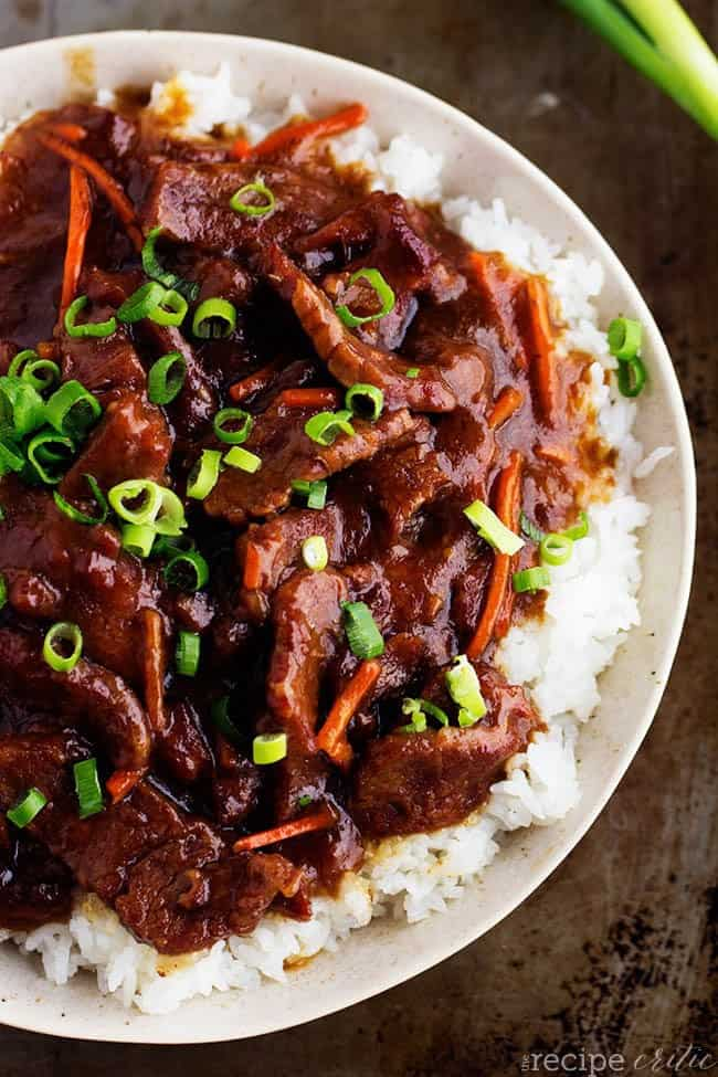 Slow cooker mongolian beef on rice and a white plate.