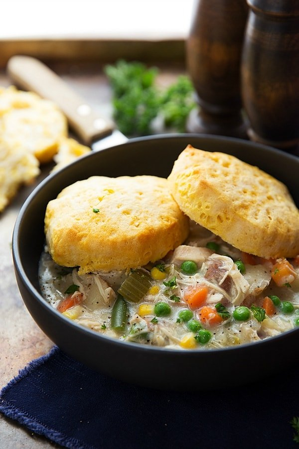 Chicken Pot Pie Soup in a bowl with 2 biscuits on top.